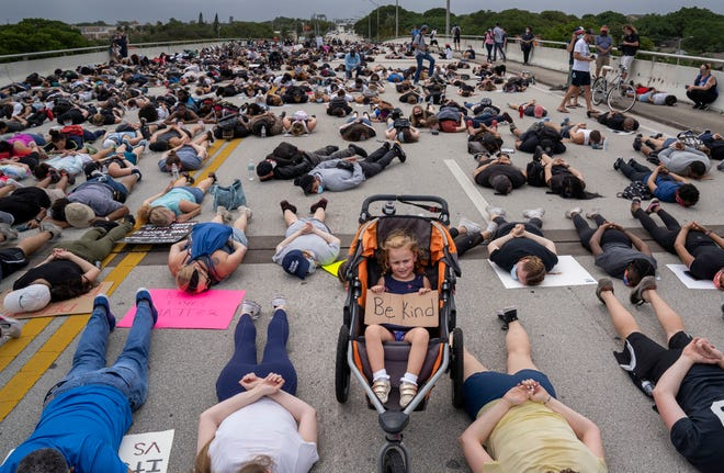 People lay down on an overpass on Southern Blvd. during a protest march in the death of George Floyd on June 6, 2020 in West Palm Beach, Fla.