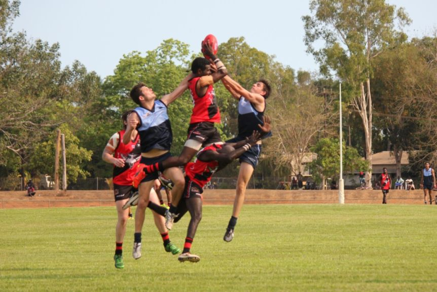 Three Tiwi Bombers players leap for the ball