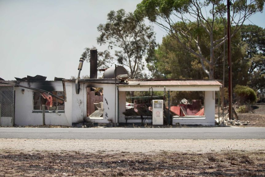A service station appears scorched by fire.
