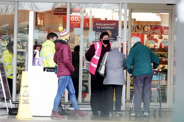 A security guard speaks to customers entering a Sainsbury's store in Swindon today on day one of the new mask crackdown