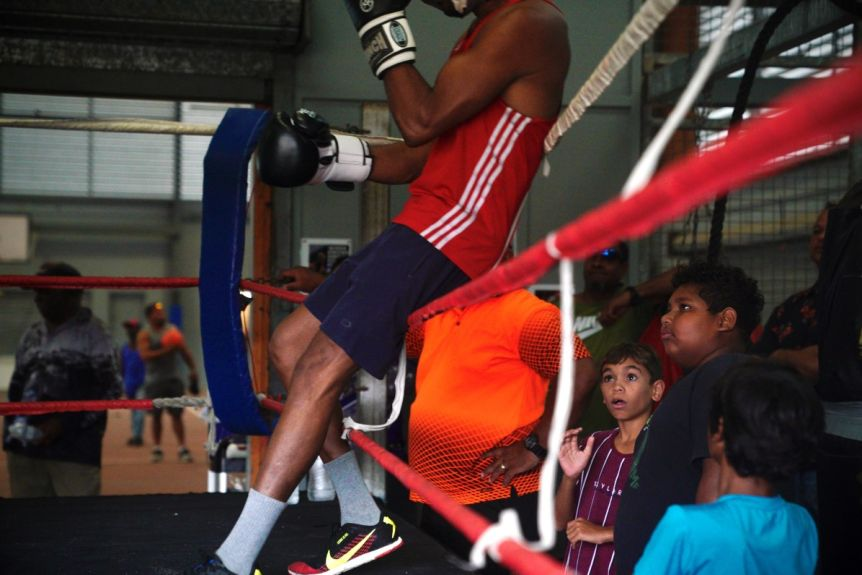 Young boy standing next to boxing ring in shock as boxer leans on ropes above him in boxing gym