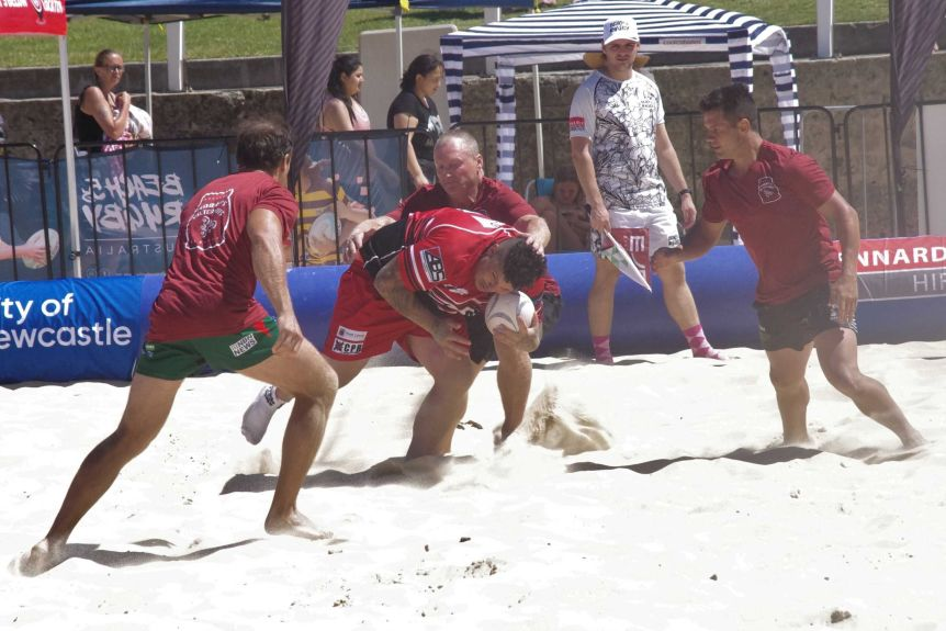 A group of male players contesting a beach rugby game at Nobbys Beach in Newcastle.