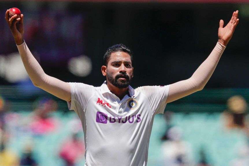Mohammed Siraj holds his hands out wide above his head, holding a red cricket ball in his right hand