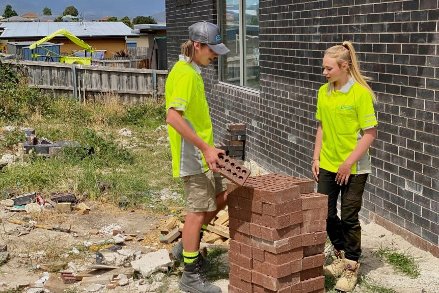 A teenage boy and teenage girl chat while moving a pile of bricks.