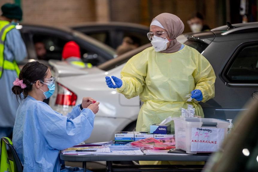 two women in scrubs and PPE holding test tubes surrounded by cars