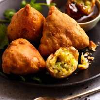Samosas on a plate with dipping sauce