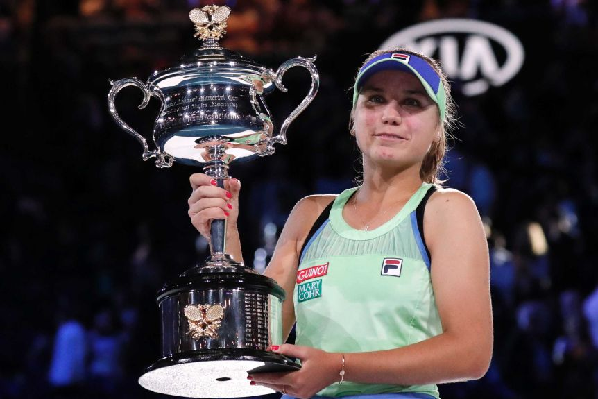 A cap-wearing tennis player holds a big trophy after winning her first Grand Slam title.