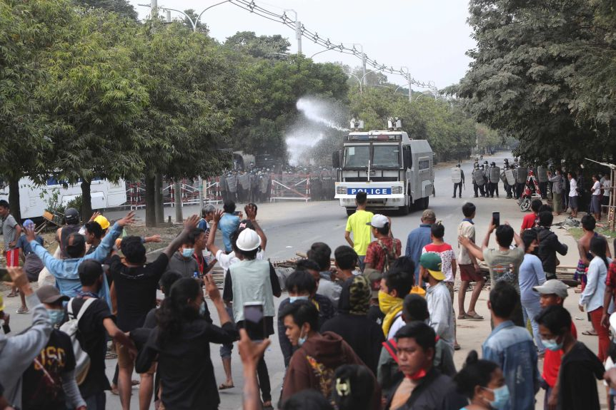 An armoured police truck uses a water cannon to disperse a crowd of protesters.
