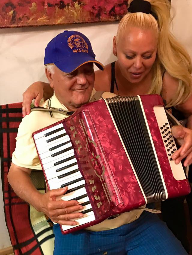 Luigi playing the piano accordion with his daughter smiling.