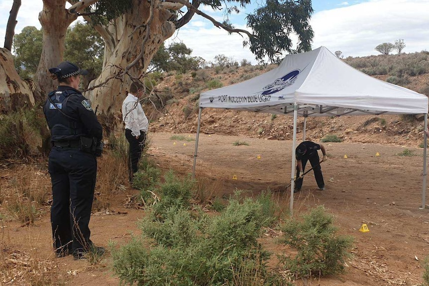 Several police officers stand and watch another police officer digging in dirt under a marquee.